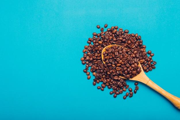 Chicchi di caffè di vista superiore in cucchiaio di legno Foto Gratuite