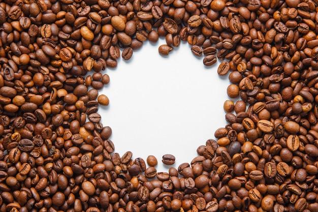 Chicchi di caffè di vista superiore in foro nel centro su fondo bianco. orizzontale Foto Gratuite