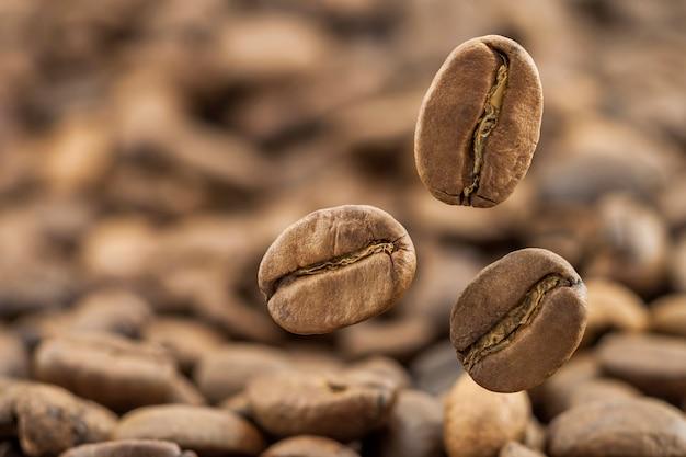 Chicchi di caffè freschi volanti come fondo con lo spazio della copia. chicchi di caffè che cadono con vapore di vapore bianco. Foto Premium