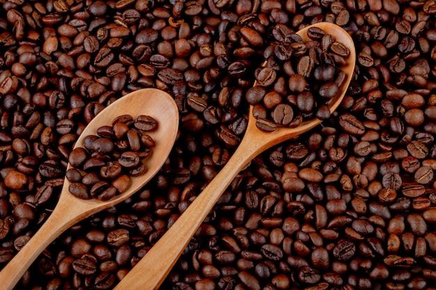Chicchi di caffè in cucchiai di legno sul fondo di vista superiore dei chicchi di caffè Foto Gratuite