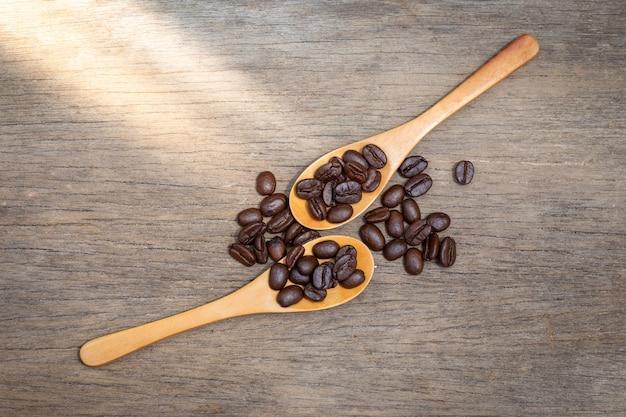 Chicchi di caffè in cucchiai di legno Foto Premium