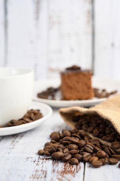 Chicchi di caffè in sacchi di canapa su una tavola di legno bianca. Foto Gratuite