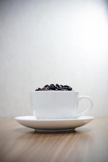 Chicchi di caffè in tazza bianca sulla tavola di legno con uso dello spazio della copia per fondo Foto Premium