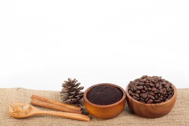 Chicchi di caffè in tazza di legno su tela da imballaggio isolata su fondo bianco Foto Premium