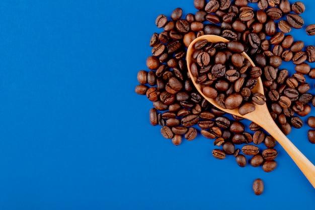 Chicchi di caffè in un cucchiaio di legno sui chicchi di caffè sulla vista superiore del fondo blu Foto Gratuite