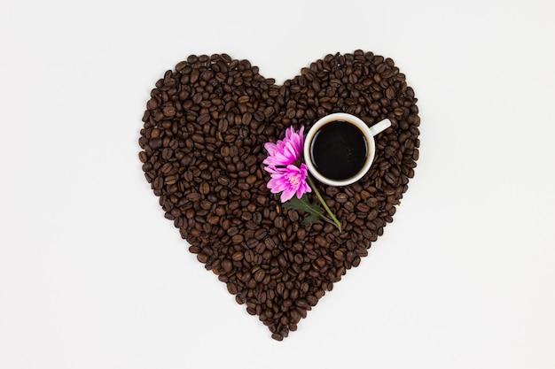 Chicchi Di Caffè In Una Forma Di Un Cuore E Fiore Su Sfondo Bianco