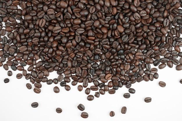 Chicchi di caffè marrone su uno sfondo bianco con spazio di copia. Foto Premium