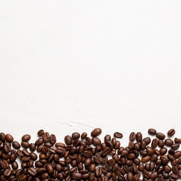 Chicchi di caffè piani di disposizione su fondo bianco con copia-spazio Foto Gratuite