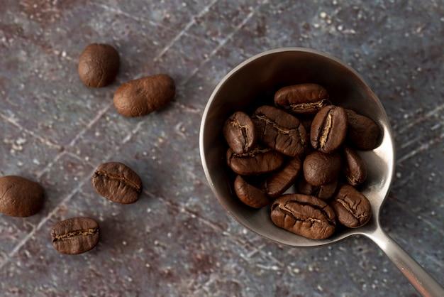 Chicchi di caffè sul cucchiaio con fondo di marmo Foto Gratuite