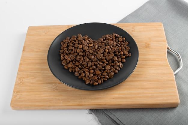 Chicchi di caffè sul piattino nero Foto Premium