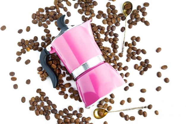 Chicco di caffè, caffettiera rosa e cucchiai su fondo bianco Foto Premium