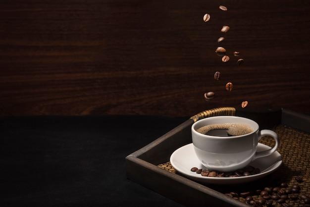 Chicco di caffè di scatteing sulla tazza di caffè con i chicchi di caffè sul vassoio di bambù Foto Premium