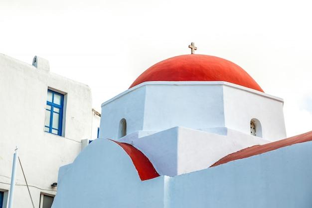 Chiesa di agia kyriaki, edificio bianco tipico della chiesa greca con cupola rossa contro il cielo blu sull'isola di mykonos, in grecia Foto Premium