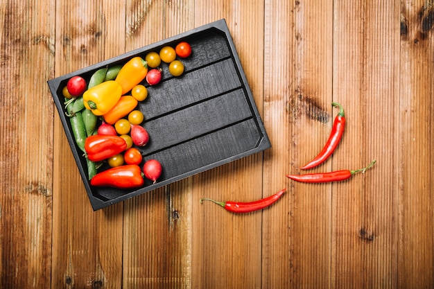Chili peppers vicino a pallet con verdure Foto Gratuite