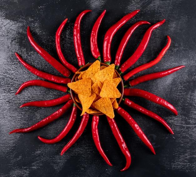 Chip di vista superiore con i peperoncini rossi in ciotola sull'orizzontale di pietra nero Foto Gratuite