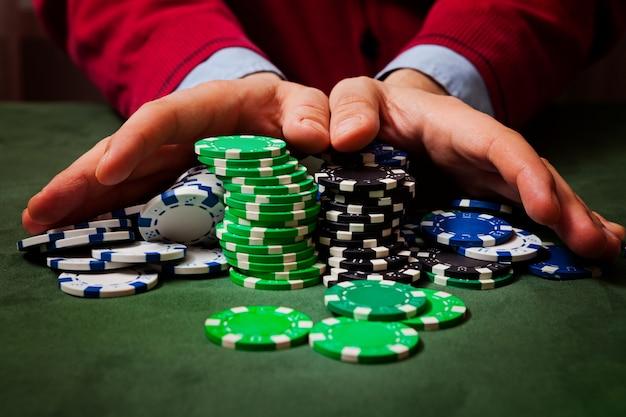 Chip in primo piano, nella sfocatura delle mani di un uomo che tiene fiches, giocando a poker Foto Premium