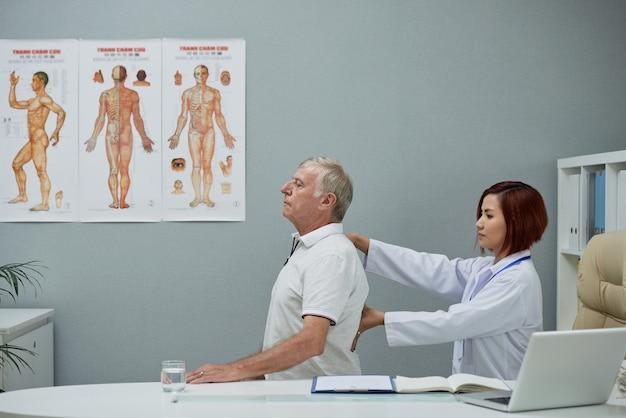 Chiropratico che controlla la colonna vertebrale Foto Gratuite