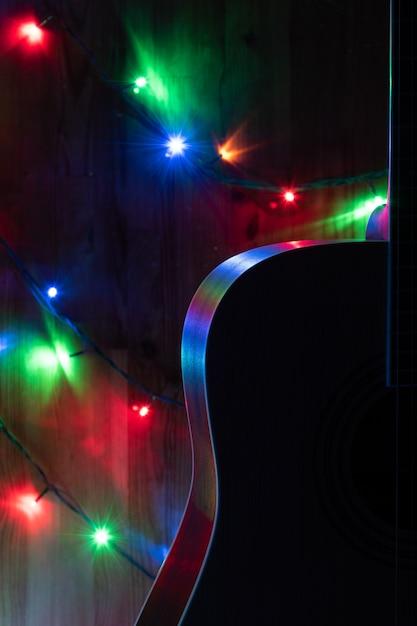 Chitarra acustica classica nelle luci natalizie in memoria della musica Foto Premium
