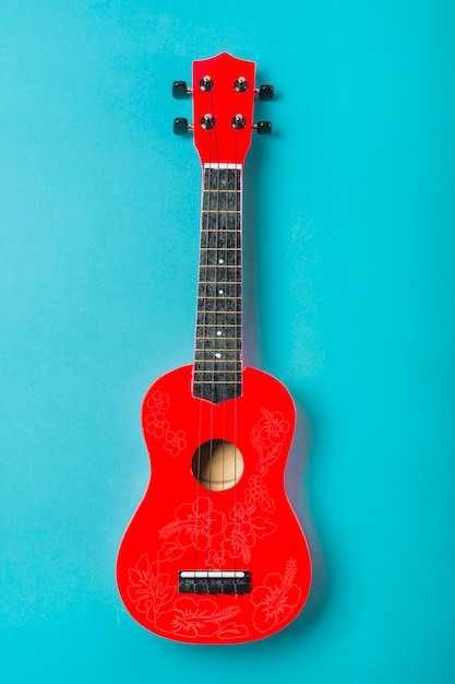 Chitarra classica acustica rossa su sfondo blu Foto Gratuite