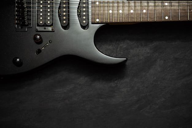 Chitarra elettrica nera sul pavimento di cemento nero. Foto Premium