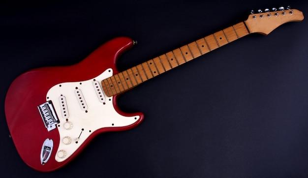 Chitarra elettrica rossa con uno sfondo nero. Foto Premium