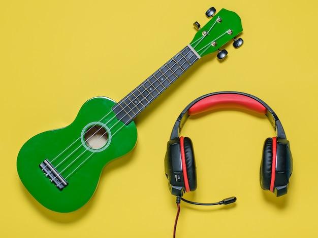 Chitarra verde delle ukulele e cuffie rosso-nere su fondo giallo. la vista dall'alto. Foto Premium