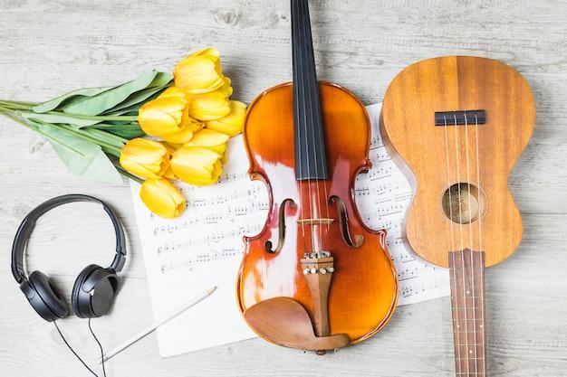 Chitarra; violino; tulipani; cuffie; matita sulla nota musicale sopra il tavolo Foto Gratuite