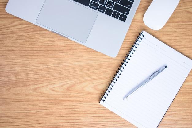 Chiuda fino alla tavola di legno marrone con il computer, il taccuino e la penna sull'immagine. Foto Premium