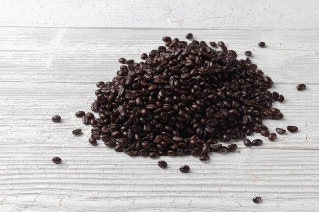 Chiuda in su dei chicchi di caffè di arrosto di mucchio sulla scheda di legno Foto Premium