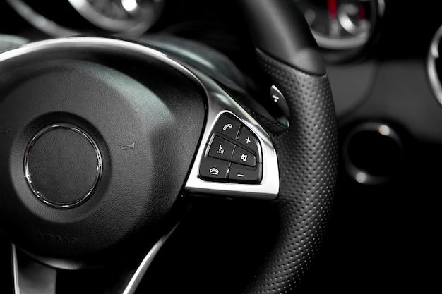 Chiuda in su dei comandi del volante in automobile di lusso moderna. interno della macchina. macchina intelligente Foto Premium