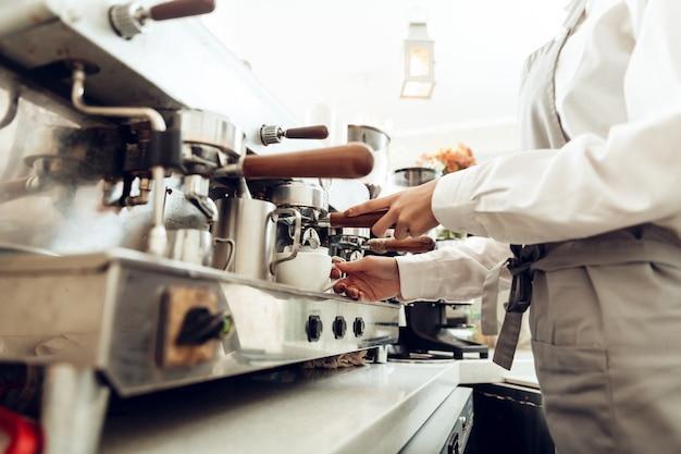Chiuda in su del barista femminile che prepara il caffè Foto Premium