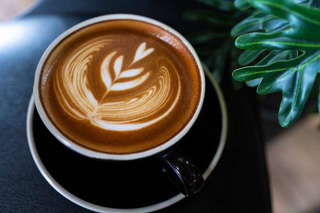 Chiuda in su del caffè di arte del latte sulla tabella di legno Foto Premium
