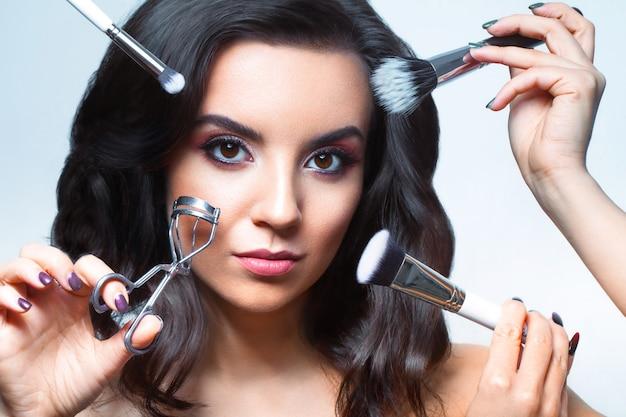 Chiuda in su del fronte della giovane donna con tutti i tipi di strumenti trucco - pennello, rossetto ecc. trucco viso bellezza Foto Premium