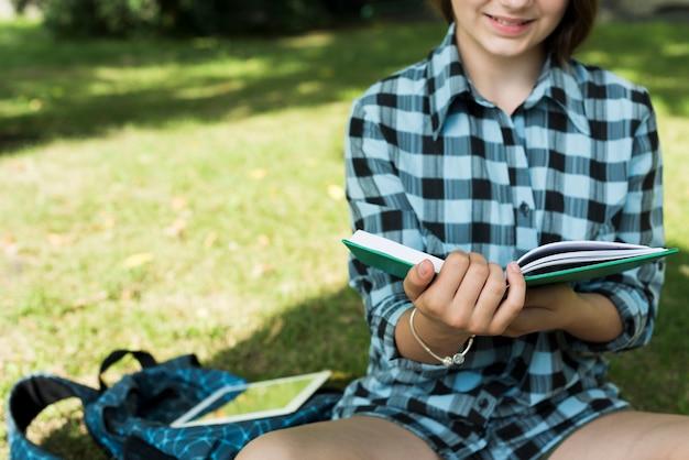 Chiuda in su del libro di lettura di seduta della ragazza della high school Foto Gratuite