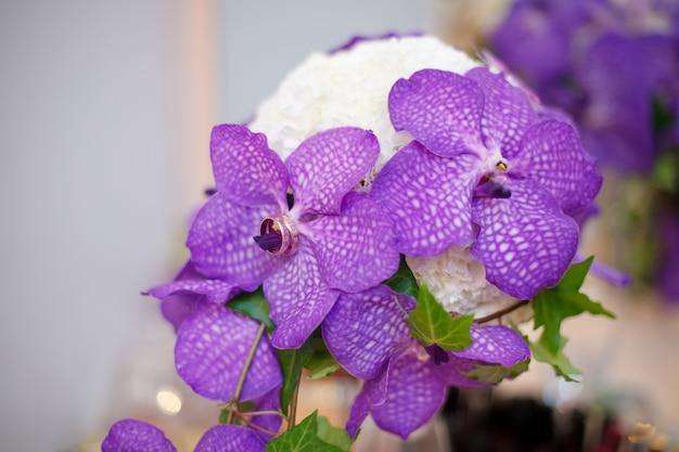 Chiuda in su del mazzo viola di cerimonia nuziale dell'orchidea con gli anelli Foto Premium