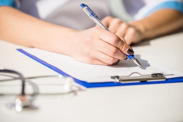 Chiuda in su del medico femminile che scrive su un computer. Foto Premium