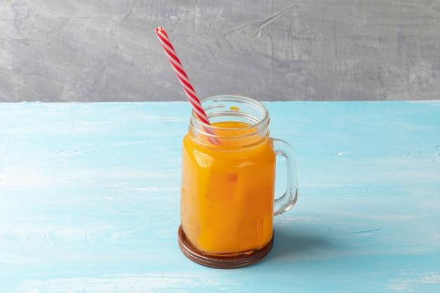 Chiuda in su del succo di arancia ghiacciato in vetro Foto Premium