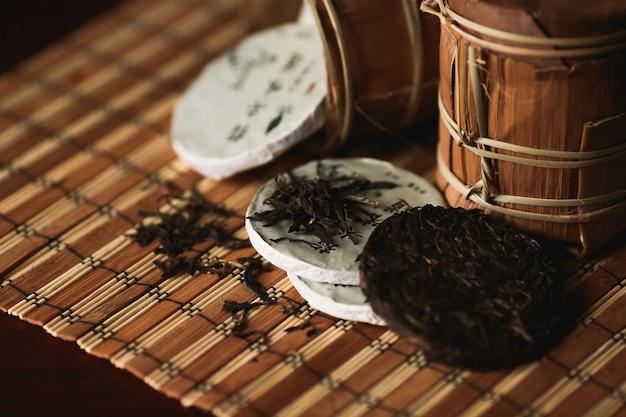 Chiuda in su del tè del puer con il rospo dorato su una stuoia di bambù. sfondo nero. Foto Gratuite