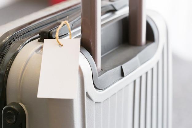 Chiuda in su dell'etichetta in bianco dell'etichetta dei bagagli su una valigia Foto Premium