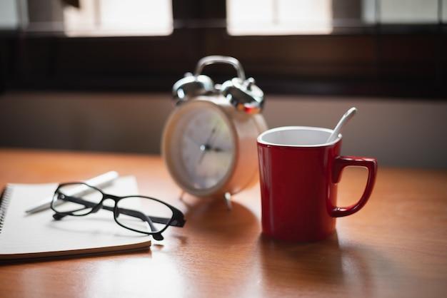 Chiuda in su dell'orologio sulla tabella dell'ufficio Foto Premium