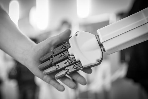 Chiuda in su dell'uomo che agita le mani con un robot Foto Premium