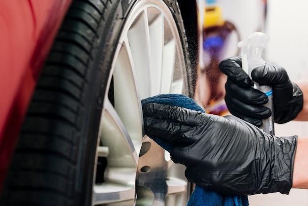 Chiuda in su dell'uomo che pulisce gli orli dell'automobile Foto Gratuite