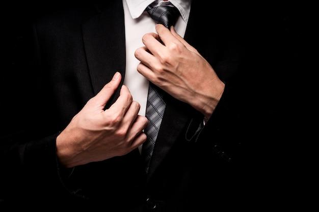 Chiuda in su dell'uomo in vestito nero, camicia e cravatta su priorità bassa nera Foto Premium
