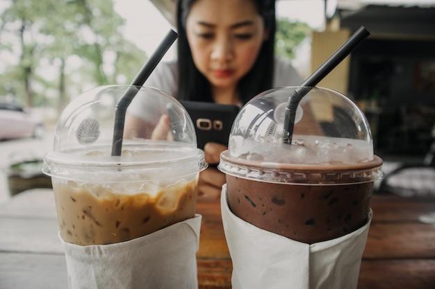 Chiuda in su della bevanda ghiacciata del cacao e del caffè in tazza di plastica sulla tabella di legno. Foto Premium