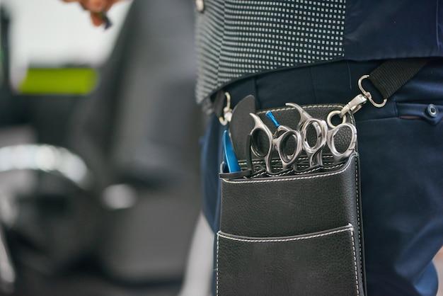 Chiuda in su della borsa di cuoio del barbiere con le forbici taglienti metalliche che appendono sulla vita. Foto Premium