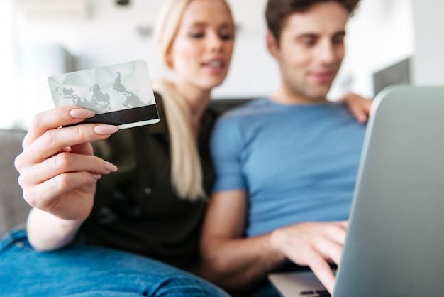 Chiuda in su della carta di credito della holding della giovane donna mentre per mezzo del computer portatile con suo marito Foto Gratuite