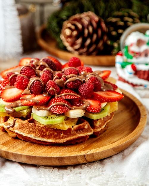 Chiuda in su della cialda con la frutta guarnita con cioccolato Foto Gratuite