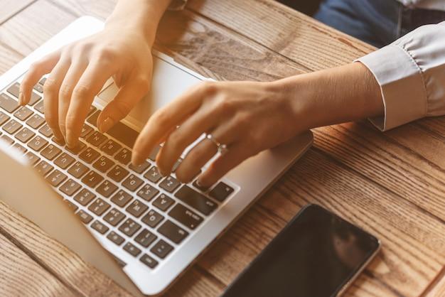 Chiuda in su della donna che digita sul computer portatile nella caffetteria Foto Gratuite