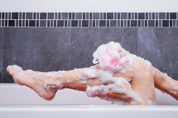 Vasca Da Bagno Rosa : Chiuda in su della donna che lava la gamba con spugna rosa nella