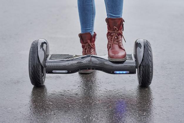 Chiuda in su della donna che usando il hoverboard sulla strada asfaltata. piedi su scooter elettrico all'aperto Foto Premium